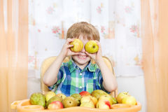 Happy boy playing with apples in front of fruits. Royalty Free Stock Image