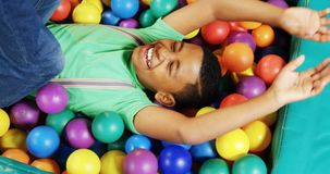 Boy playing in ball pool 4k. Happy boy playing in ball pool 4k stock video footage