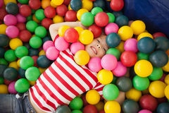Happy boy playing in ball pool Stock Photos