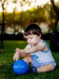 Happy boy playing with ball and toy car on green grass royalty free stock photo