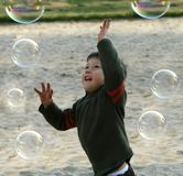 Happy boy playing with bubbles Stock Photo