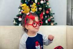 Happy boy playing with Christmas decorations. Happy young boy smiling, playing and having fun with Christmas decorations and a Christmas tree in the background Stock Photo