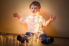 Happy boy playing with Christmas lights. Happy boy playing on the floor with Christmas lights Stock Image