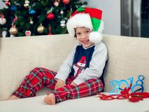 Happy boy playing with a Christmas tree in the background royalty free stock photography