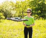 Happy boy playing with flying drone with camera controlled by sm stock photography