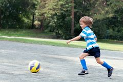 Happy boy playing football. Outdoor Stock Images