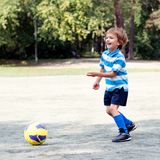 Happy boy playing football Stock Photo