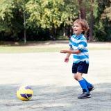 Happy boy playing football Stock Photo