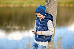 Happy boy playing game on smartphone outdoors Stock Photos