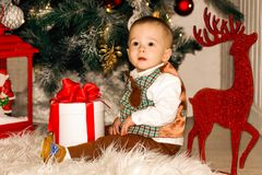 Happy boy playing with gifts near Christmas tree royalty free stock photography