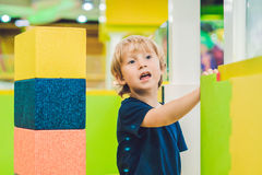 Happy boy playing indoors with big plastic construction blocks Stock Image