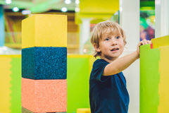 Happy boy playing indoors with big plastic construction blocks Royalty Free Stock Photography