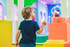 Happy boy playing indoors with big plastic construction blocks Royalty Free Stock Image