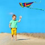 Happy boy playing with kite on summer field Royalty Free Stock Photos