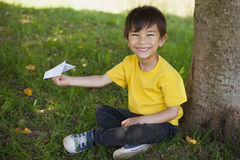 Happy boy playing with a paper plane at park Stock Image