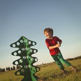 Happy boy playing with paper tree Stock Image