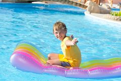 Happy boy playing in pool stock photography