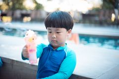 A happy boy is playing at the pool. A happy asian boy is playing at the pool Royalty Free Stock Photo