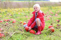 Happy boy playing on pumpkin field Royalty Free Stock Image