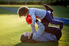 Happy young boy playing with red ball and his mother on green grass Stock Image
