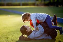 Happy young boy playing with red ball and his mother on green grass Stock Photo