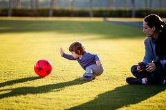 Happy young boy playing with red ball and his mother on green grass Stock Images