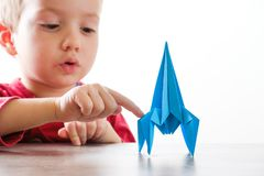 Happy boy playing with rocket. Happy child boy playing with handmade origami paper rocket Stock Images