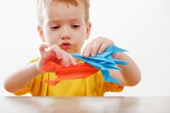 Happy boy playing with rocket. Happy child boy playing with handmade origami paper rocket Royalty Free Stock Images