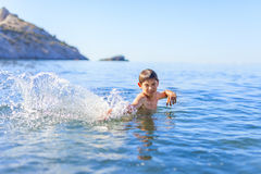 Happy boy playing in the sea Royalty Free Stock Images