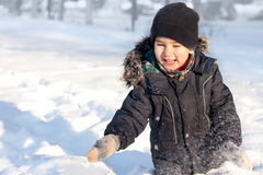 Happy boy playing in snow Stock Photos