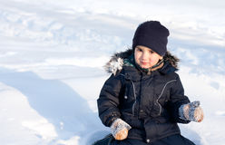 Happy boy playing in snow Stock Photo