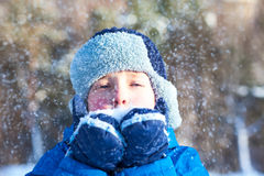 Happy boy is playing with snow Stock Photo