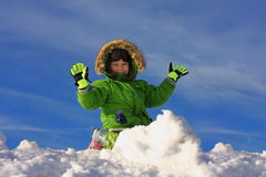 Happy Boy Playing In Snow. Smiling boy in a green parka and green gloves, hands upraised, kneeling behind a pile of snow.  Blue sky background Royalty Free Stock Photo