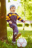Happy boy playing with soccer ball at park Stock Images