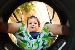 Happy boy playing in swing. Happy caucasian boy playing outdoors in a car tire swing, seen from below Royalty Free Stock Photos