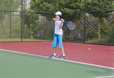 Happy Boy  is  playing tennis in the tennis court Royalty Free Stock Photos