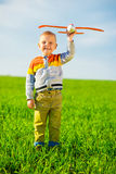 Happy boy playing with toy airplane against blue Stock Image