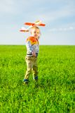 Happy boy playing with toy airplane against blue Royalty Free Stock Image