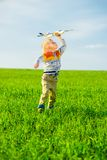 Happy boy playing with toy airplane against blue. Happy kid playing with toy airplane against blue summer sky background. Boy throw foam plane in green field royalty free stock photography