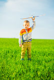 Happy boy playing with toy airplane against blue Royalty Free Stock Photo