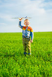 Happy boy playing with toy airplane against blue summer sky and green field background. Royalty Free Stock Images