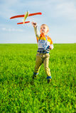 Happy boy playing with toy airplane against blue summer sky and green field background. Stock Photos
