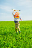 Happy boy playing with toy airplane against blue summer sky and green field background. Stock Image