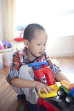 Happy boy playing toy car at home Stock Image