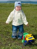 Happy boy playing with toy truck. Happy smiling kid playing with toy truck outside on the grass Royalty Free Stock Image