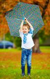 Happy boy playing under an autumn rain Stock Images
