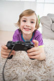 Happy boy playing video game while lying on rug Stock Image