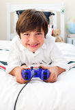 Happy boy playing video games. In his bedroom Stock Photos