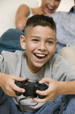 Happy Boy Playing Video Games At Home. Closeup of a cheerful little boy playing video games with happy blurred mother in the background at home Royalty Free Stock Image