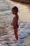 A happy boy is playing in the waves on the beach. Cheerful boy bathes in the sea waves at sunset stock images